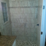 A different view of a custom tiled shower with a glass block window