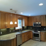 A beautiful new hickory kitchen using Pioneer cabinets, Cambria counters, Kitchen Aid appliances and a glass backsplash all sitting on a new porcelan tile floor