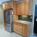 A view of the new Kitchen Aid refrigerator surrounded by a pantry cabinet and stunning hickory cabinets