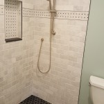 Tumbled marble shower with a niche and a Moen hand held shower arm